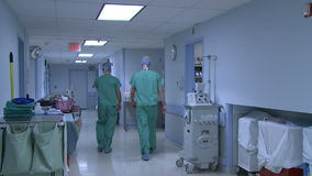 Two male doctors head to surgery. Two male doctors walk to surgery stock video footage