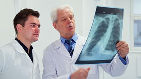 Two male doctors look at x-ray stock video footage