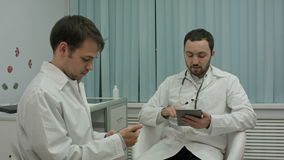 Two male doctors at medical cabinet using mobile stock video