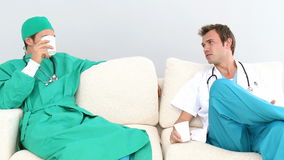 Two male doctors in a staff room. Two male doctors sitting on a sofa in a staff room stock video footage