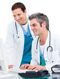 Two male doctors working at a computer Stock Images