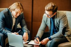Two male employees consulting with laptop in cafe Royalty Free Stock Photo