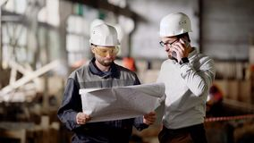 Two male engineers standing in the building site and holding construction plan. Designer speaking on the telephone. Two male engineers dressed in protective stock footage