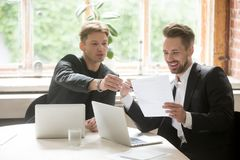 Two male executive coworkers looking at marketing plan document. Positive project manager and CEO discussing corporate opportunities, planning new business stock photos