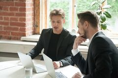 Two male executives looking at laptop screen during business mee. Ting. Businessmen discuss corporate goals in front of laptops at workplace in office. Analyzing Stock Photography