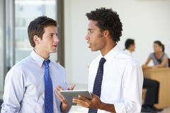 Two Male Executives Looking At Tablet Computer With Office Meeting In Background Royalty Free Stock Image