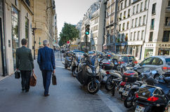 Two male executives walk along Rue de Turbigo in Paris, France Stock Images
