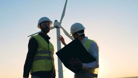 Two male experts are having a discussion in front of windmill. Clean, eco-friendly energy concept. Two male experts are having a discussion in front of an stock video footage
