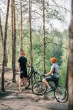 two male extreme cyclists in helmets with mountain bikes resting with sport bottles of water stock image