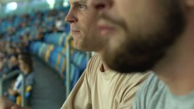 Two male fans cheering for national football team, leisure activity with friends. Stock footage stock video