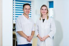 Two Male and Female Doctors or Nurses Standing Inside Hospital Building. Royalty Free Stock Images