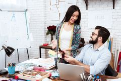 Two fashion designers looking at bow ties. Two male and female fashion designers looking at bow ties Royalty Free Stock Image