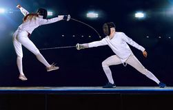 Two fencing athletes fight on professional sports arena stock photos