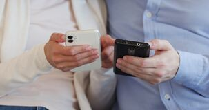 Two male and female users holding smartphones using apps, closeup