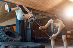 Two Male fitness models training workout witth heavy and big tire and hammer indoor fitness center Stock Photo