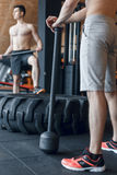 Two Male fitness models training workout witth heavy and big tire and hammer indoor fitness center Royalty Free Stock Photos
