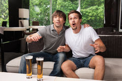Two male football fans cheering football team. Stock Photography