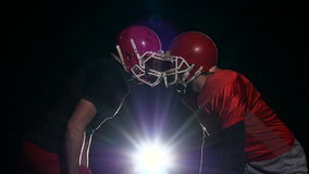 Two male footballer face their protective helmets. Black background. Slow motion stock footage