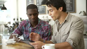 Two Male Friends In Coffee Shop Looking At Digital Tablet stock footage