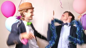 Two male friends dancing in photo booth. Two young male friends enjoying dancing in photo booth stock video footage