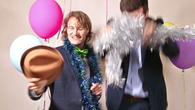Two male friends dancing in photo booth. Two young male friends enjoying dancing in photo booth stock footage