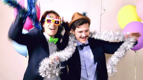 Two male friends dancing in photo booth. Two young male friends enjoying dancing in photo booth, graded stock footage
