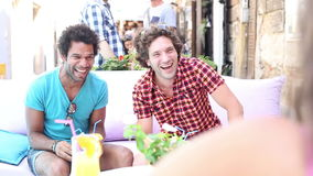 Two male friends drinking cocktails on terrace cafe in summer stock footage