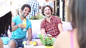Two male friends drinking cocktails on terrace cafe in summer stock video footage