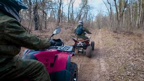 Two male friends driving ATV and moving along the road in the forest one after another. Riders are having trip and stock video footage