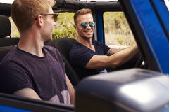 Two Male Friends Driving Open Top Car On Country Road Stock Photos