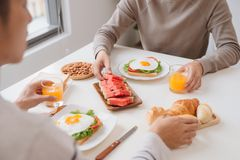Two male friends eating breakfast at home in morning. stock image