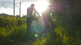 Two male friends giving high five each other and start riding bikes through meadow path in sunset. Friends cycling stock footage