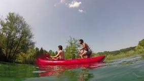Two male friends having fun in a canoe stock footage