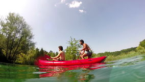 Two male friends having fun in a canoe. Split shot of two male friends having fun in a canoe on a beautiful sunny day, graded stock video