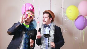 Two male friends having fun with props stock video