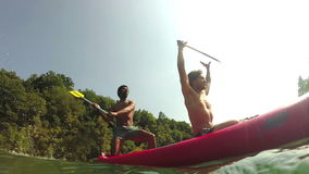 Two male friends having fun waving with paddles in a canoe stock footage