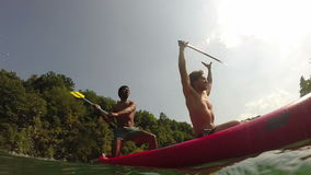Two male friends having fun waving with paddles in a canoe. Split shot of two young male friends having fun waving with paddles in a canoe on beautiful summer stock footage