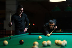 Two male friends playing billiard game in club Stock Photos