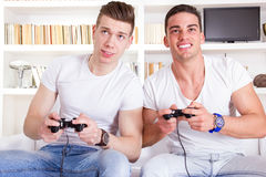 Two male friends playing video game with controllers Stock Photo