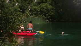 Two male friends riding canoe and splashing their female friends with paddles. Two young male friends having fun riding canoe and splashing their female friends stock footage