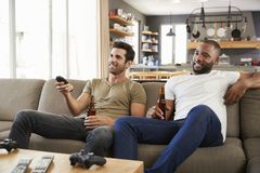 Two Male Friends Sit On Sofa And Watch Sports On Television Royalty Free Stock Photos