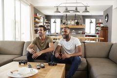 Two Male Friends Sit On Sofa And Watch Sports On Television Royalty Free Stock Image