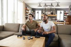 Two Male Friends Sit On Sofa And Watch Sports On Television Stock Images