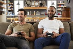 Two Male Friends Sitting On Sofa In Lounge Playing Video Game Royalty Free Stock Images