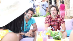 Two male friends sitting on terrace cafe in summer stock footage
