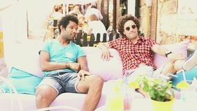 Two male friends sitting on terrace cafe in summer stock video