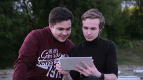 Two male friends with tablet computer talking surfing outdoors. HD stock video