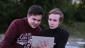 Two male friends with tablet computer talking surfing outdoors. HD stock video footage