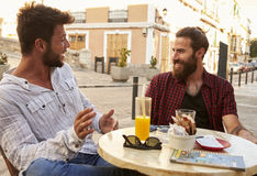 Two male friends taking at a table outside a cafe in Ibiza Royalty Free Stock Photos