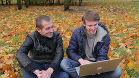 Two male friends use laptop and smiling in autumn park. Two male friends use laptop and smiles in autumn park stock footage